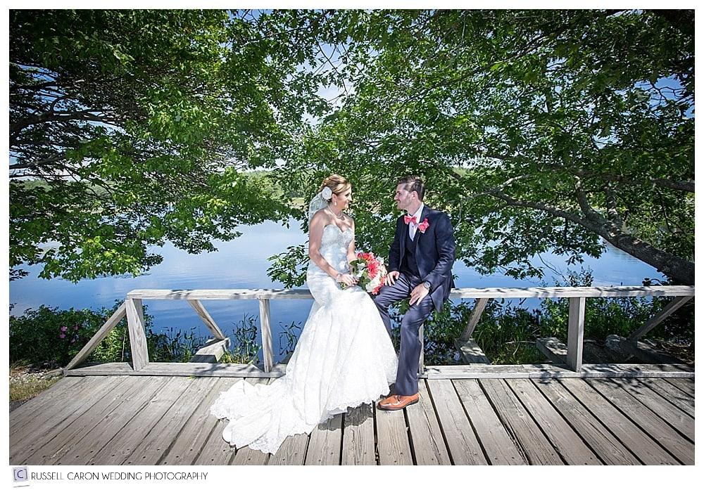 bride-and-groom-sitting-near-pond