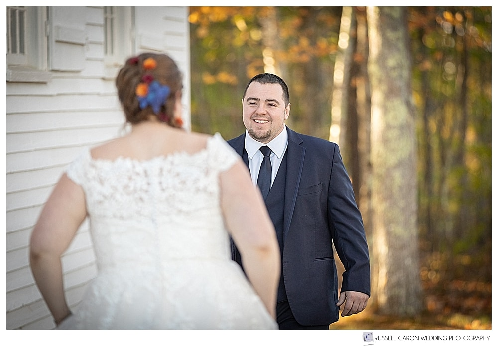 Groom waking towards bride during first look photos