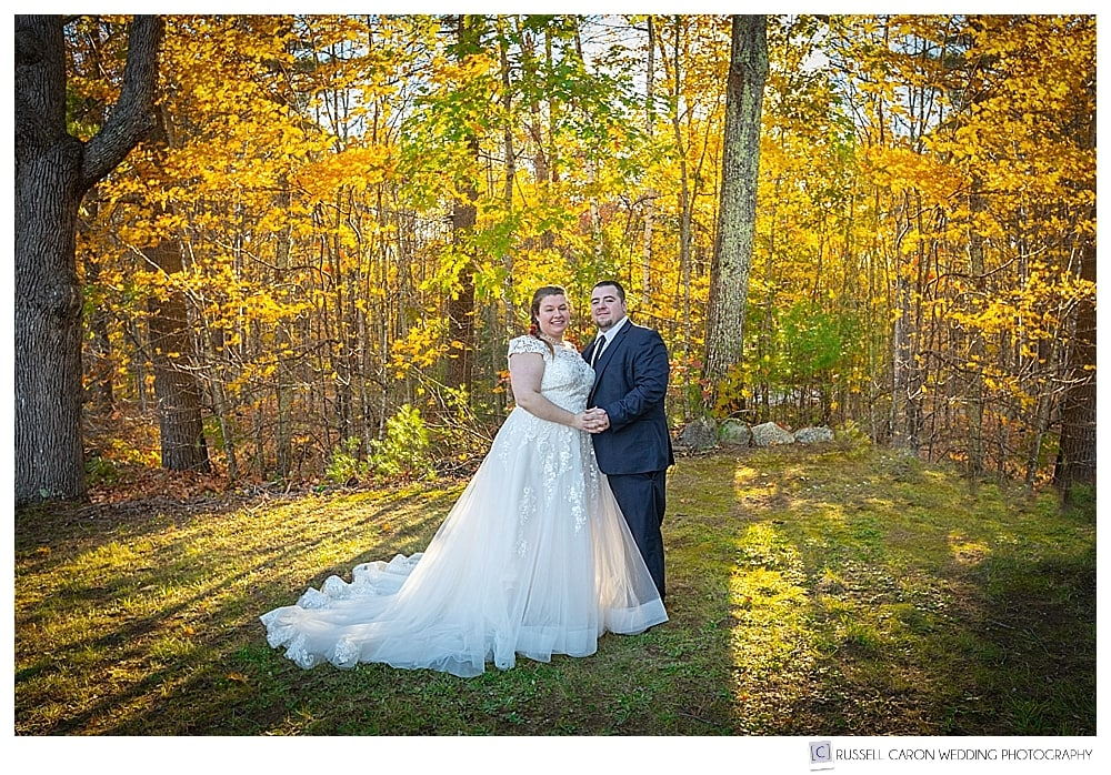 bride and groom standing together in beautiful fall foliage