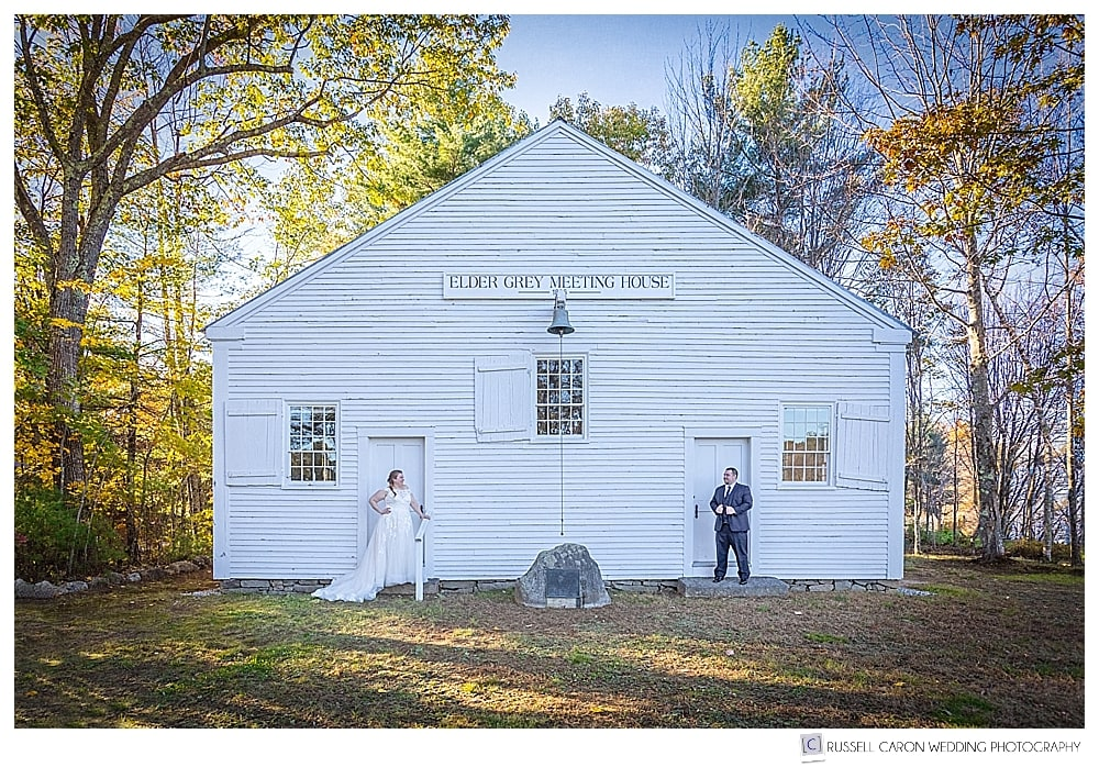 bride and groom standing in front of white clapboard meeting house at their southern Maine wedding