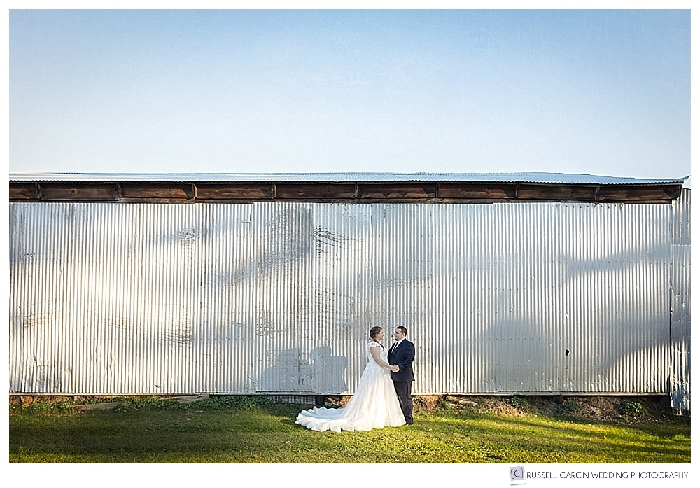 bride and groom standing in front of corrugated barn
