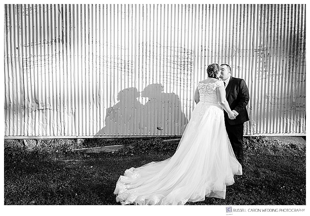 black and white photo of bride and groom standing in front of a corrugated barn