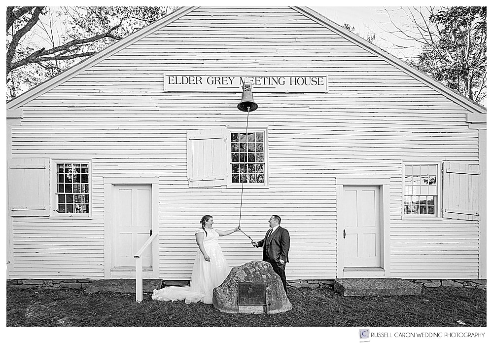 black and white photo of bride and groom ringing the bell outside of their southern maine wedding ceremony at the Elder Grey Meeting House in North Waterboro