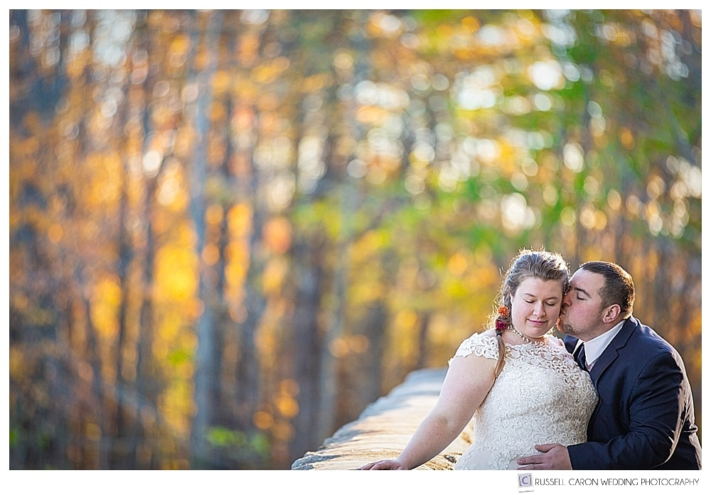 groom kissing bride with fall foliage all around