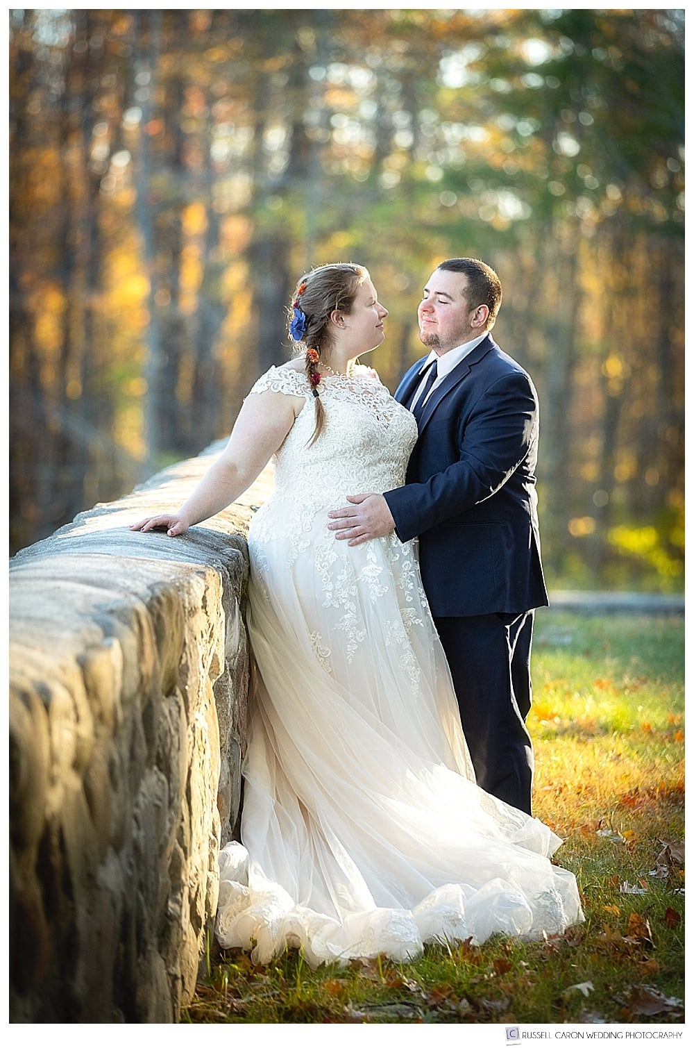 bride and groom standing at a stone wall in the fall foliage
