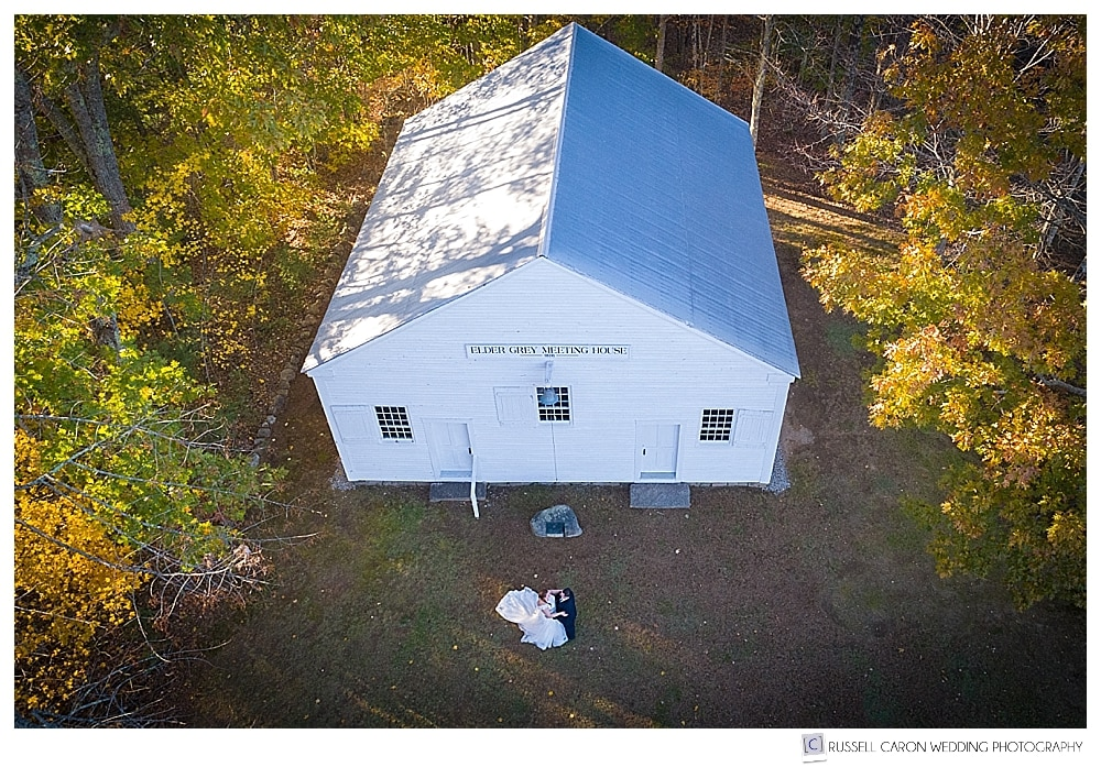 maine drone wedding photo of a bride and groom standing in front of the Elder Grey Meeting House in North Waterboro, Maine, with beautiful fall foliage
