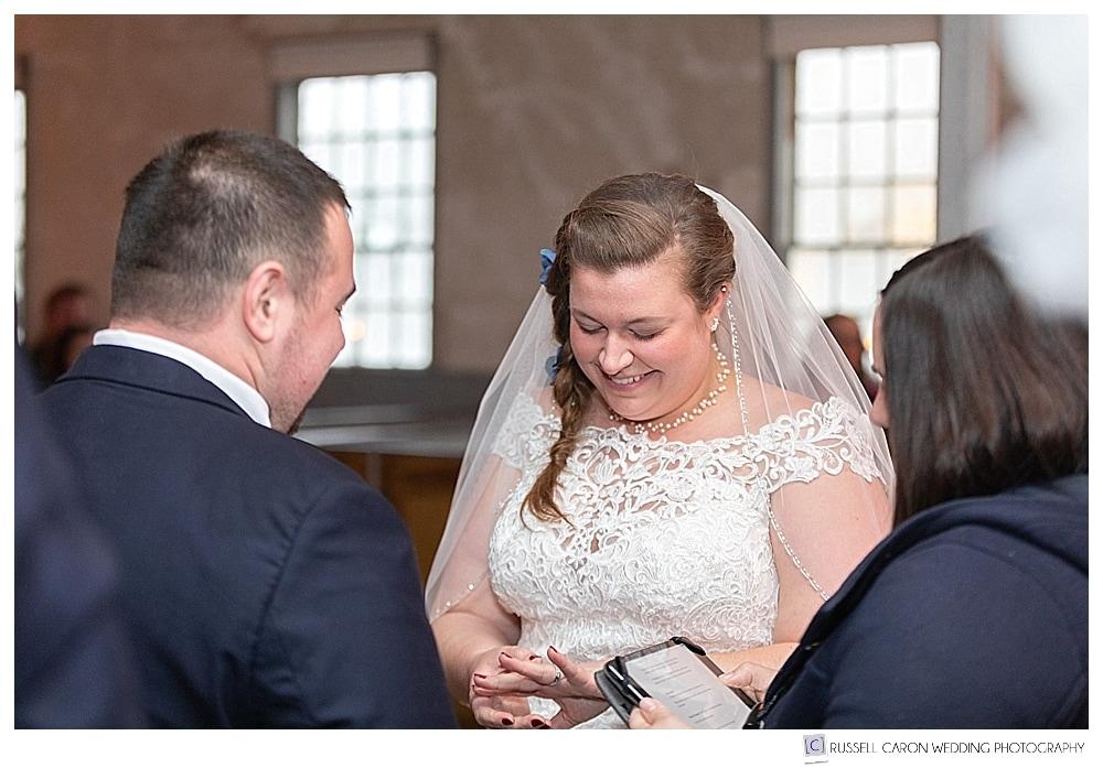 smiling bride looking at wedding ring