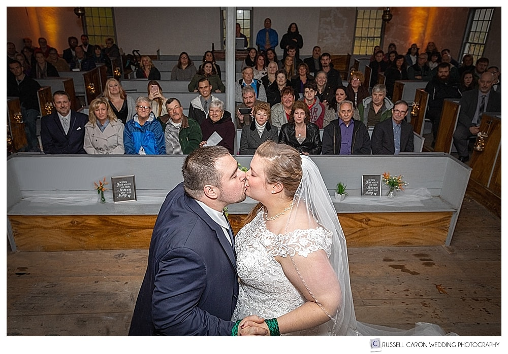 bride and groom's first kiss as wedding guests look on at the Elder Grey Meeting House, North Waterboro, Maine