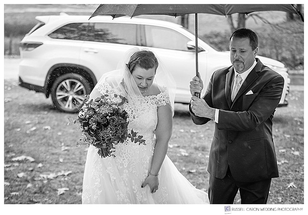 black and white photo of bride's dad holding an umbrella over her head