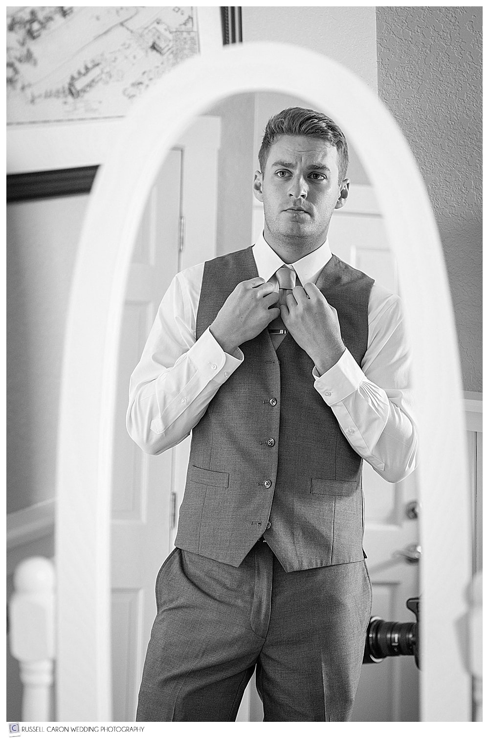 groom fixing tie in mirror