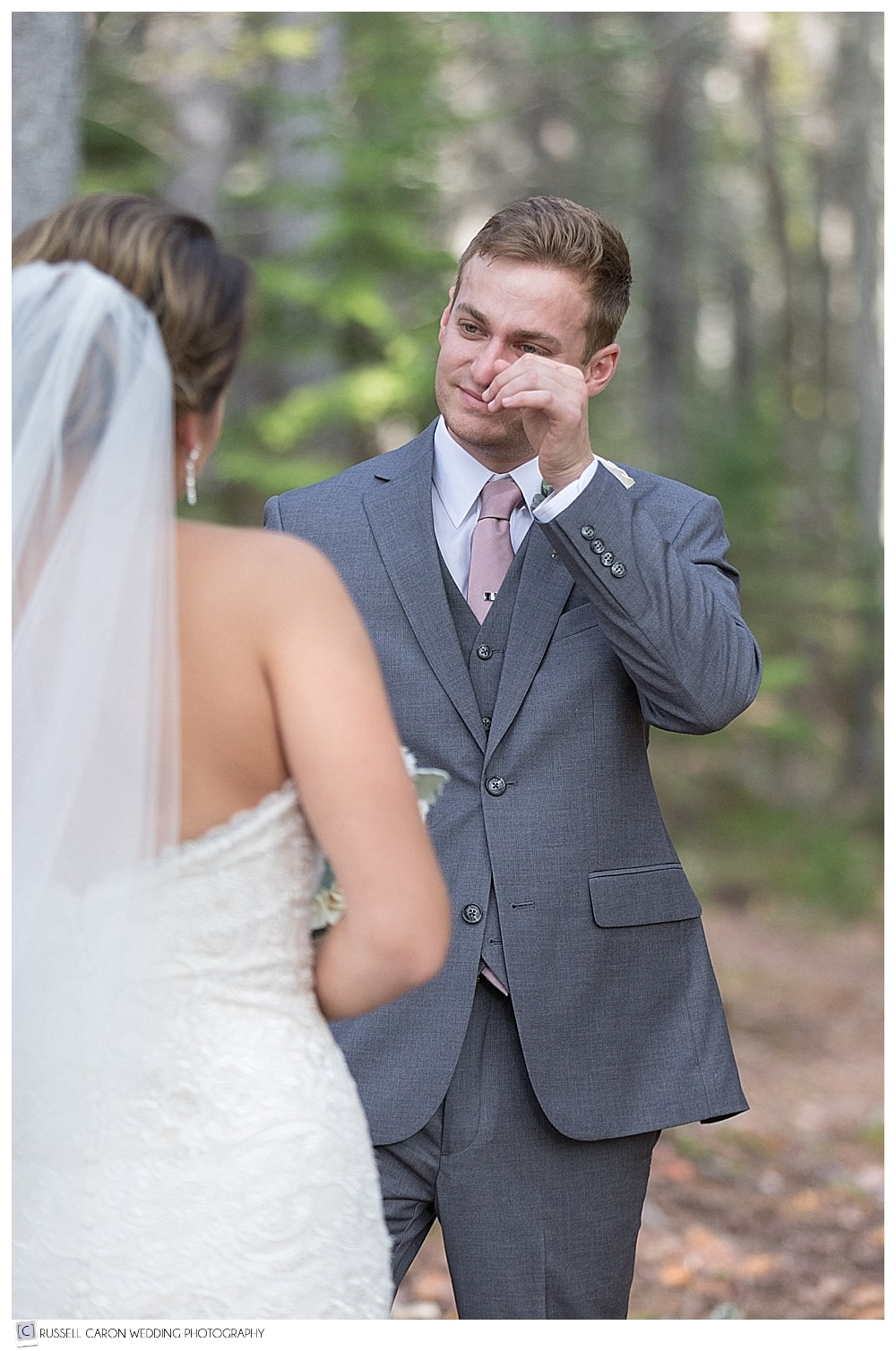 groom wipes a tear during first look