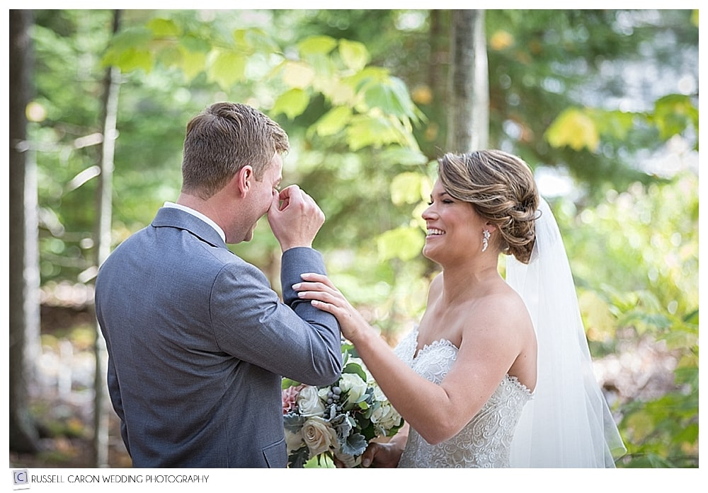 groom wipes a tear during wedding day first look