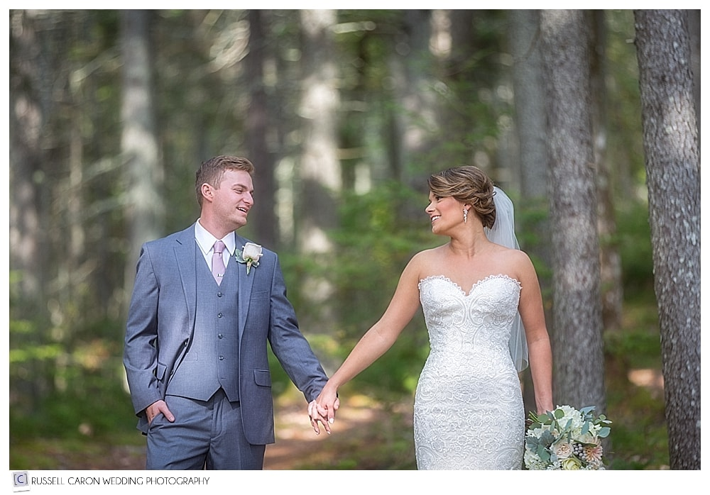 bride and groom holding hands in the woods