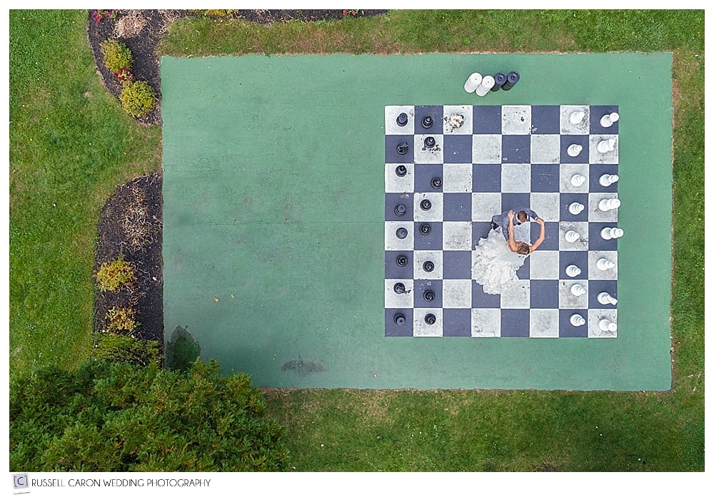 Maine drone wedding photograph of a bride and groom dancing on giant checker board at their Spruce Point Inn Resort wedding