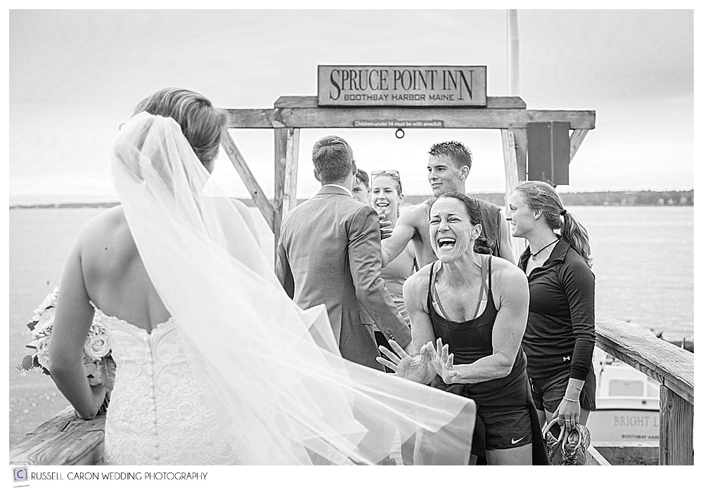 bride and groom greeted by family on the dock at their Spruce Point Inn Resort wedding