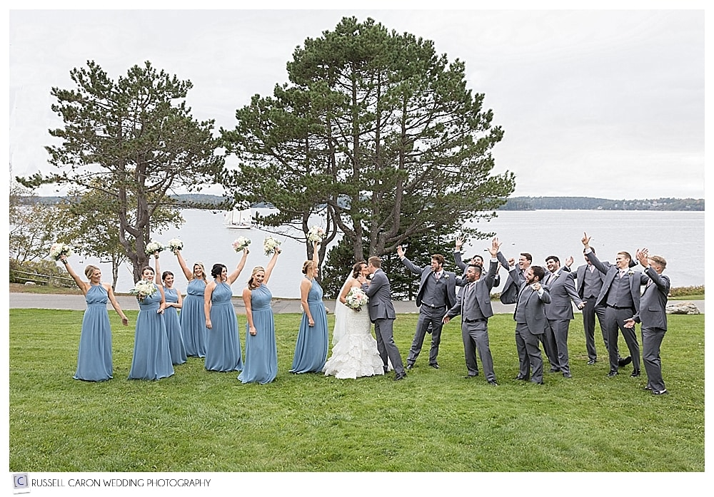 bridal party cheering as the bride and groom kiss