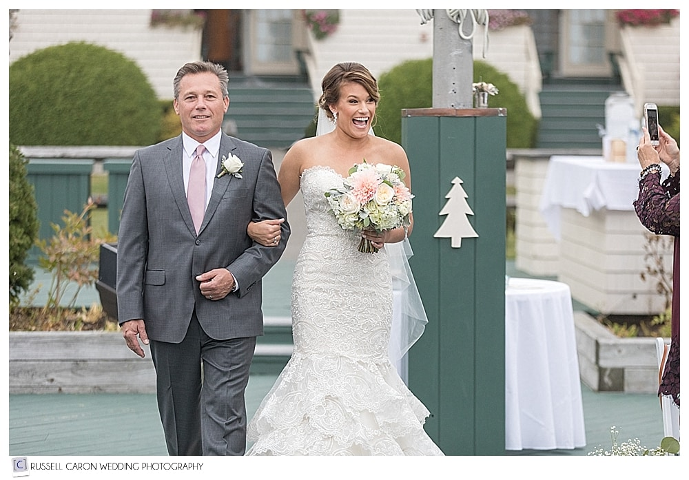 bride smiles at guest as she walks down the aisle