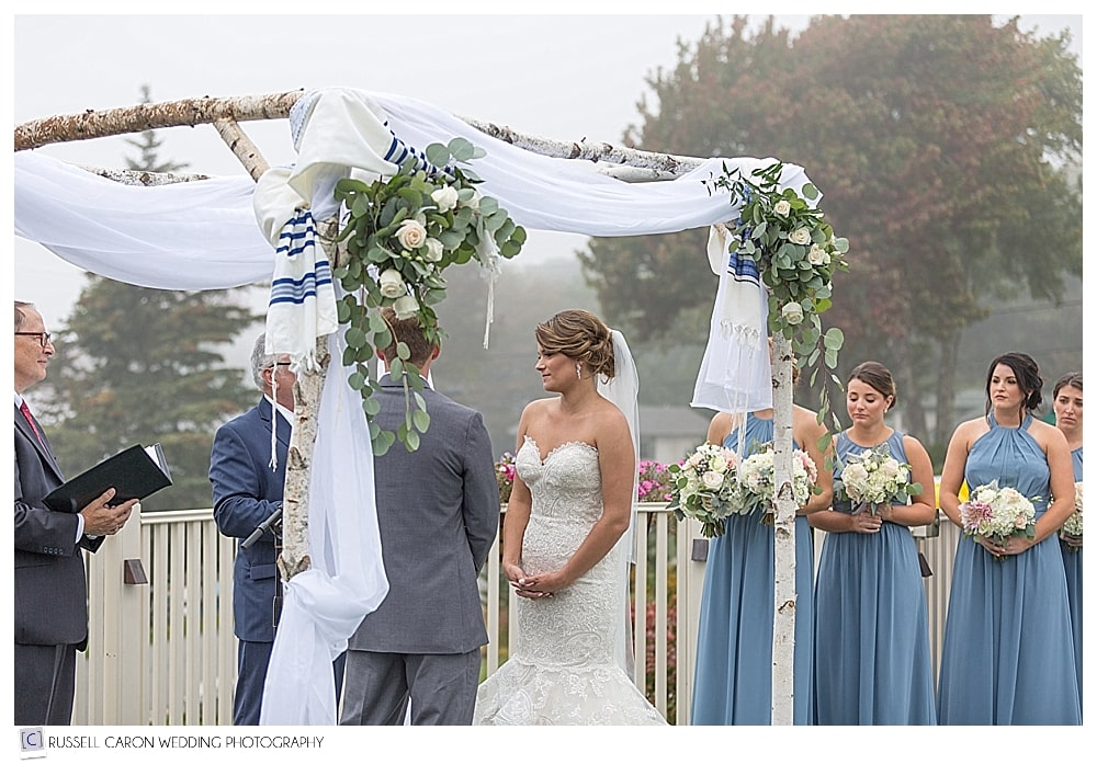 bride and groom stand under the chuppah at their Spruce Point Inn Resort wedding, Boothbay Harbor, maine