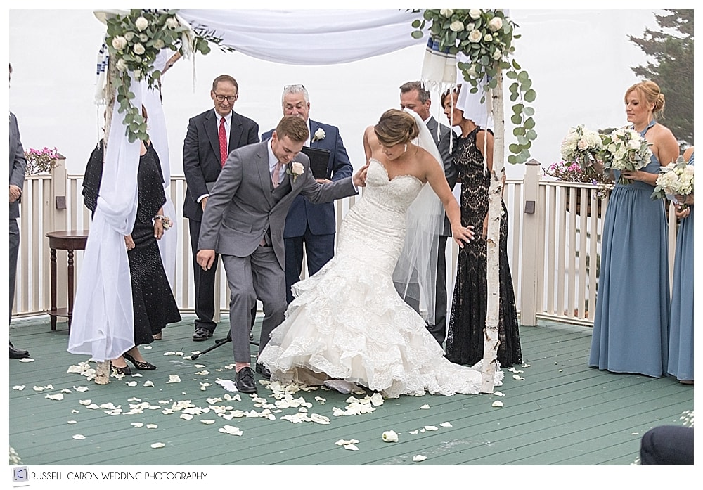 bride and groom crush glasses during wedding ceremony