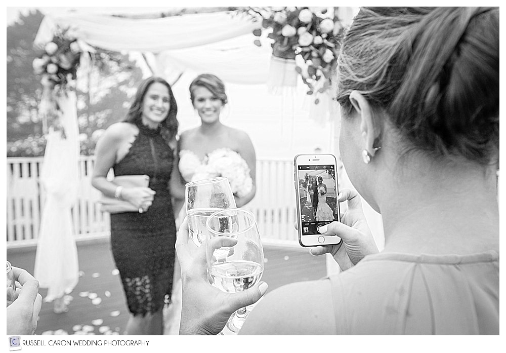 wedding guest takes phone photo of the bride