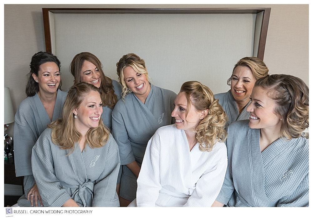 bride and bridesmaids in robes on the bed