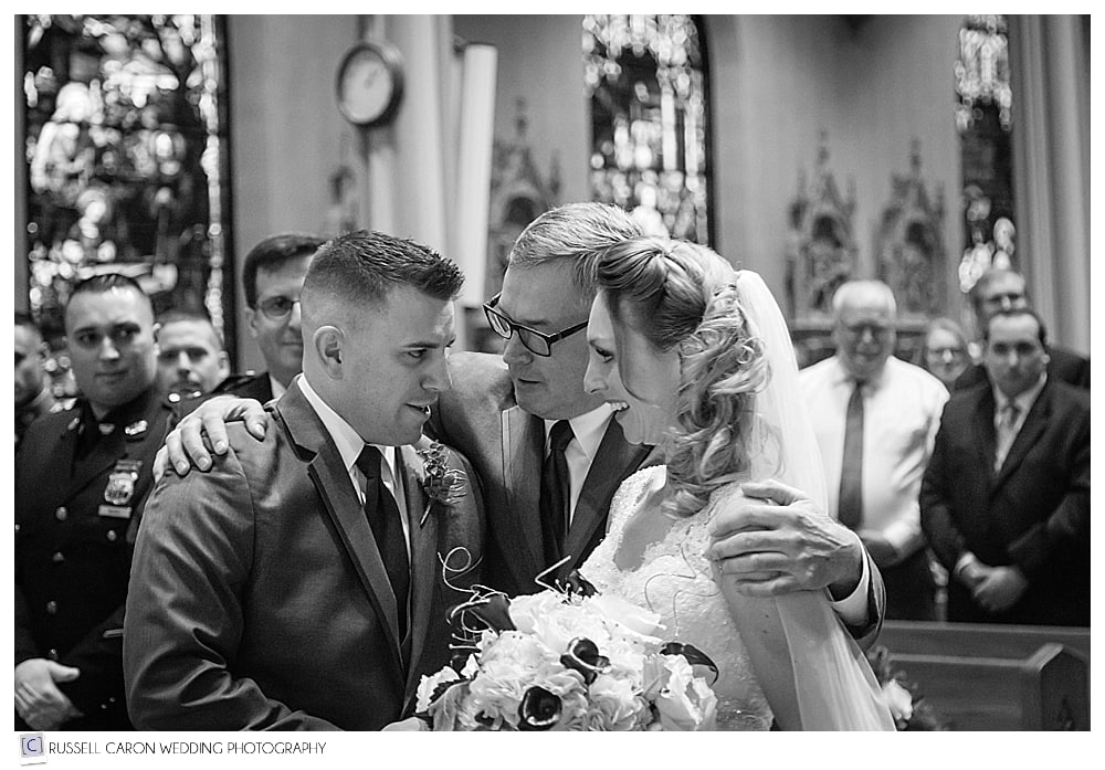 bride and father and groom at the altar