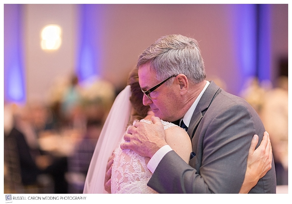 father hugs daughter during father daughter dance