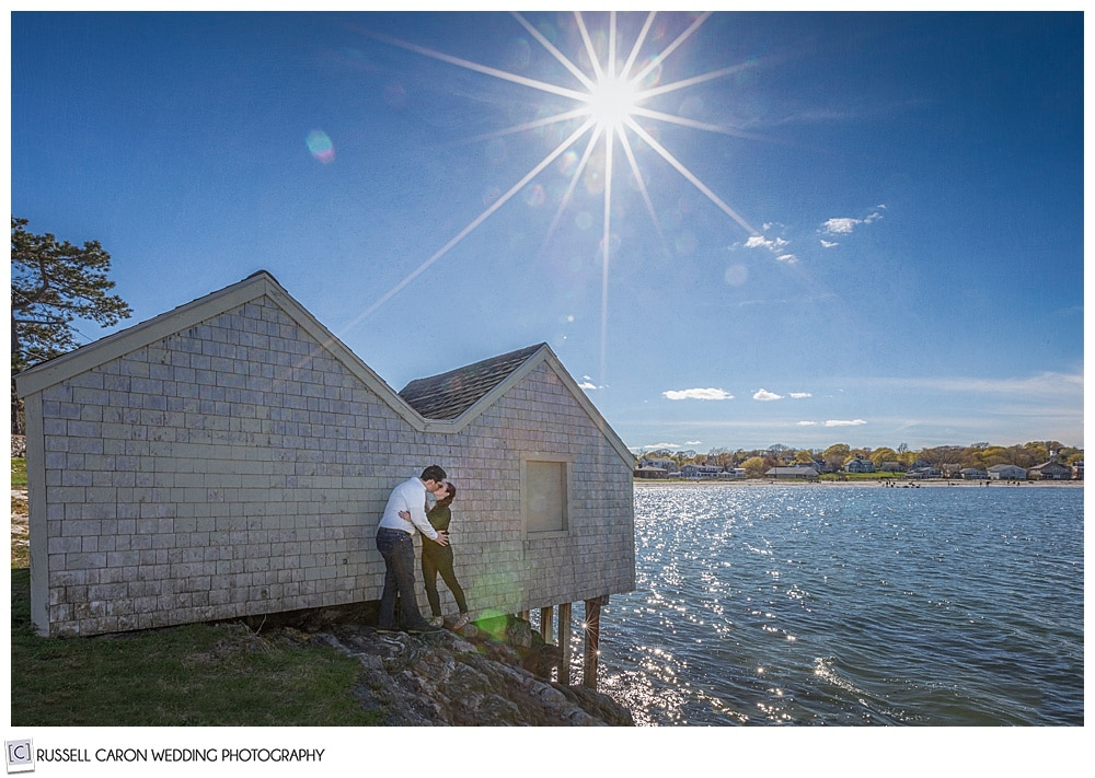 a man and woman are kissing each other in front of a building at willard beach, south Portland Maine