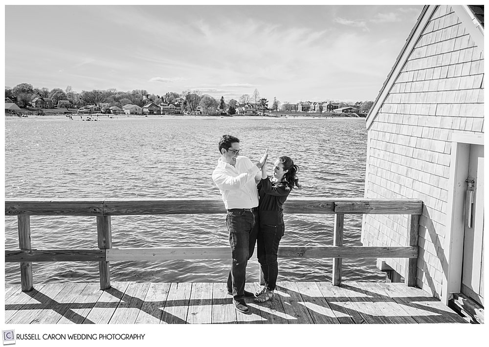 a black and white photo of a man and woman giving each other a high five at willard beach engagement session