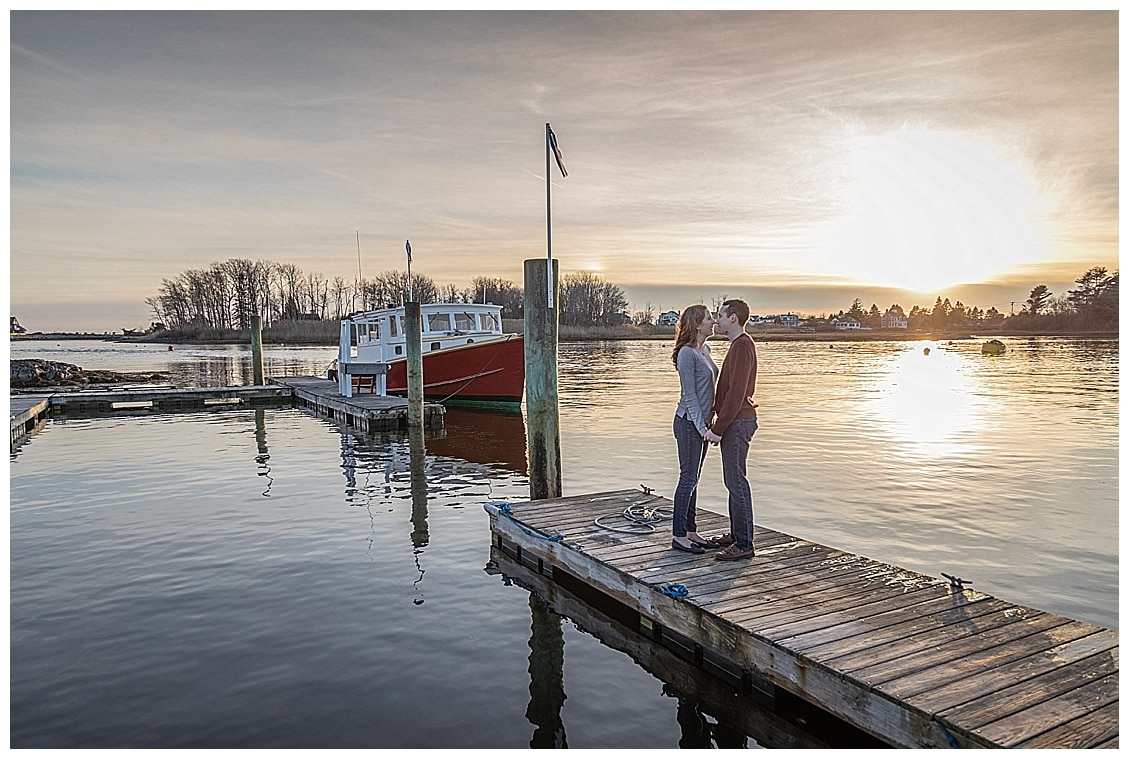 man and woman standing on a dock with the sun glowing on the water