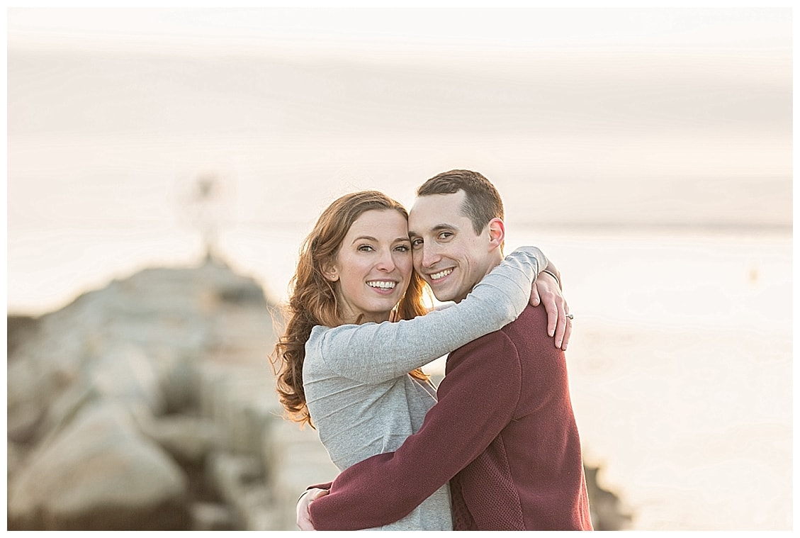 woman and man hugging, and smiling, on the Kennebunkport, Maine breakwater