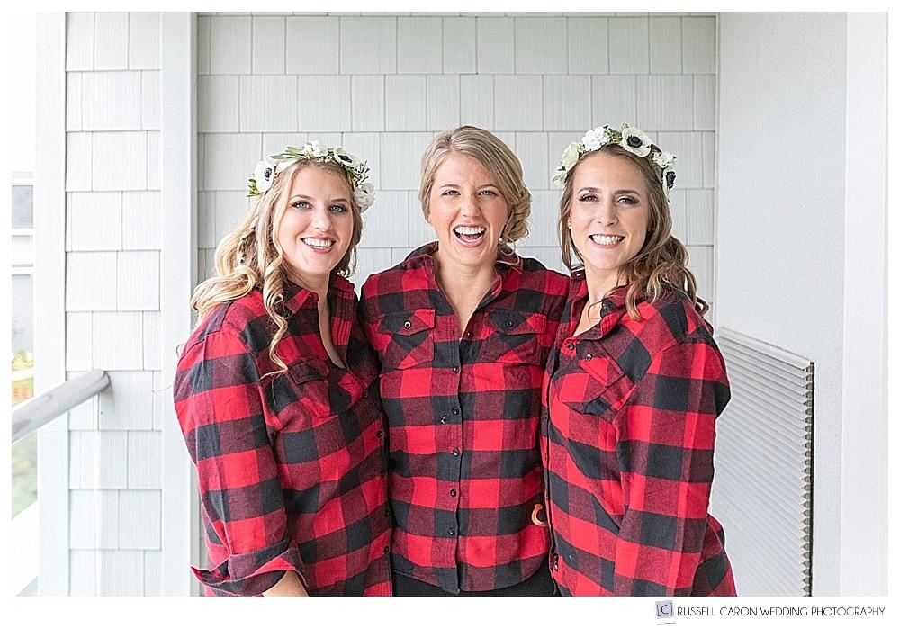 three women wearing red and black buffalo plaid shirts