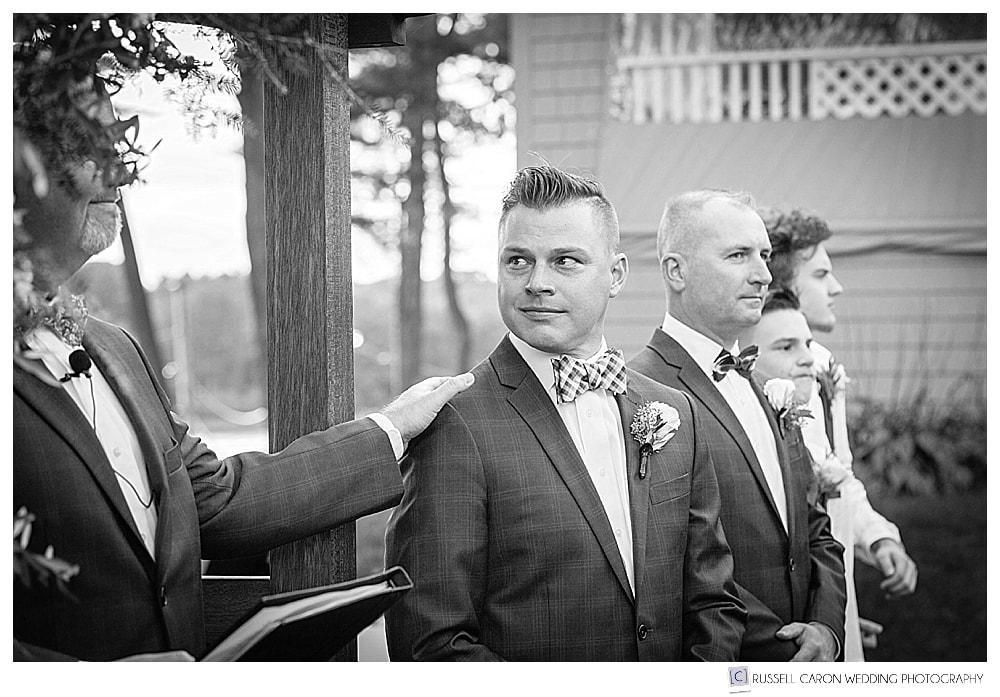 black and white photo of officiant putting his hand on groom's shoulder