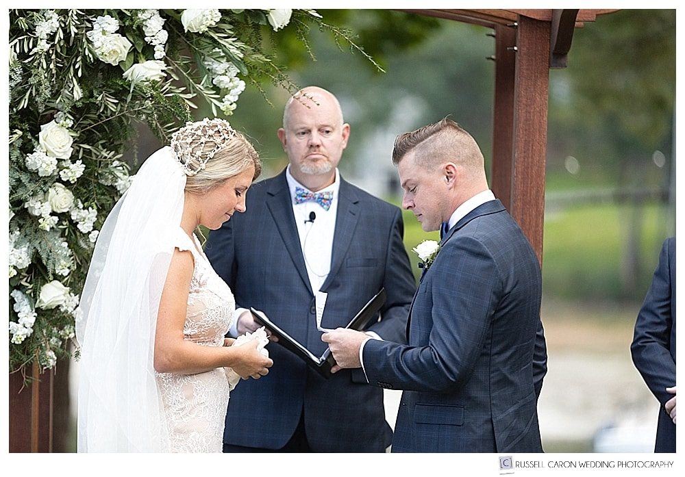 bride and groom with officiant during outdoor wedding ceremony