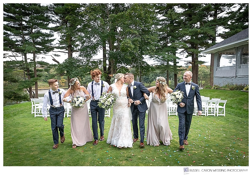 bride and groom kissing and walking arm in arm with bridal party