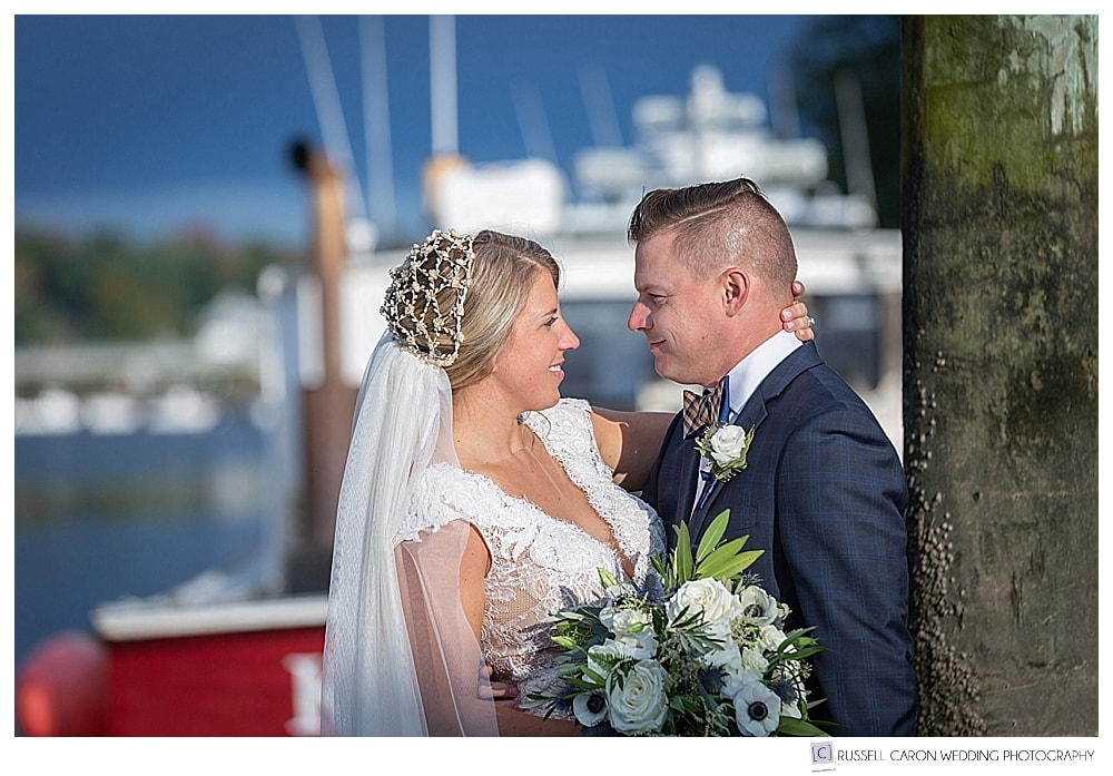bride and groom standing together on a dock