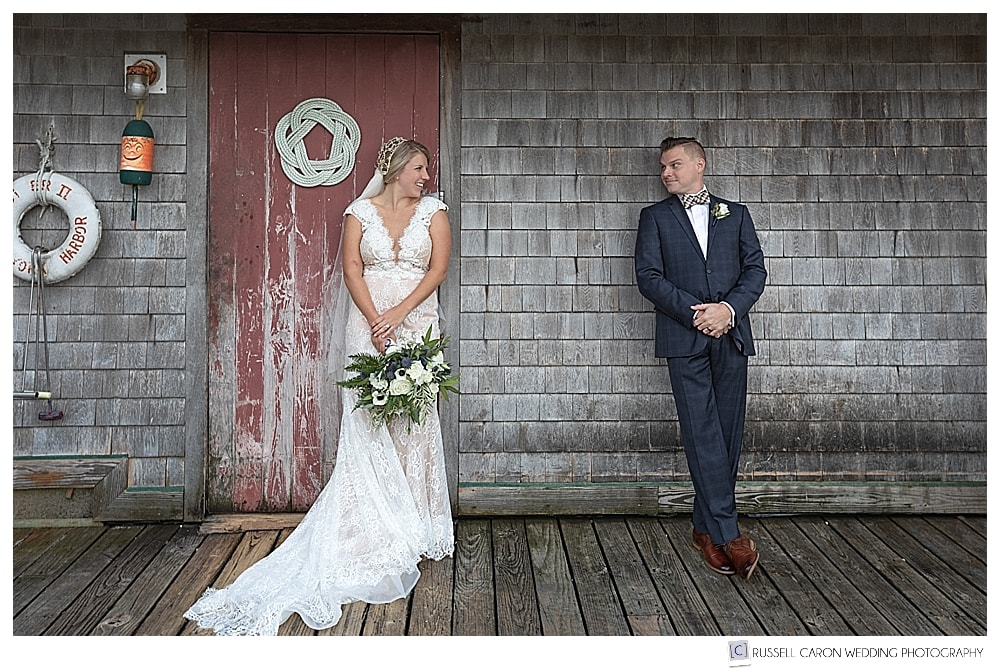 bride and groom leaning against a weathered building looking at each other