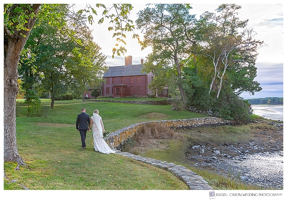 bride and groom walking along a wall with red house in background