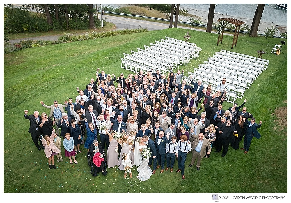 Maine drone wedding photo of bride and groom kissing while guests cheer all around them at York Golf and Tennis Club wedding ceremony