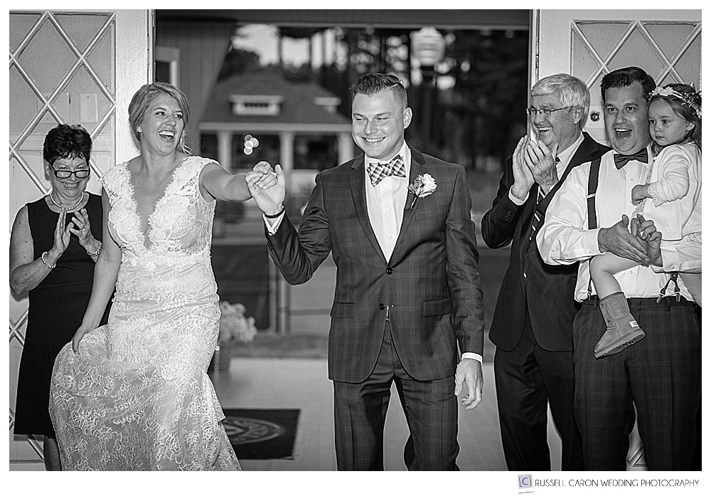 black and white photo of bride and groom entering their wedding reception at York Golf and Tennis Club