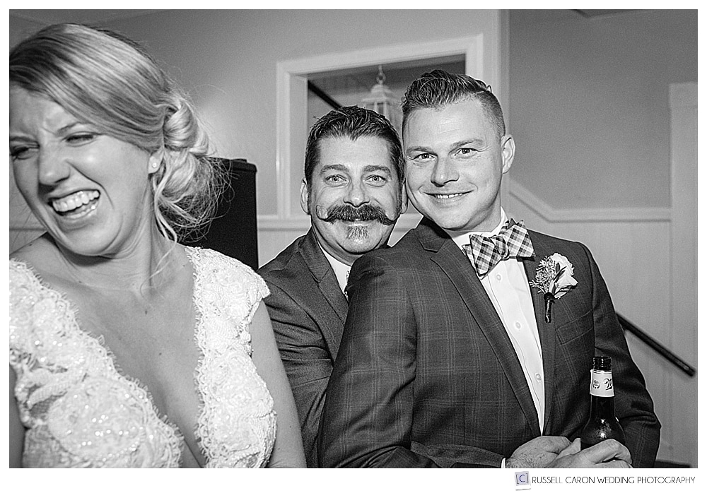 black and white photo of bride and groom laughing with a friend