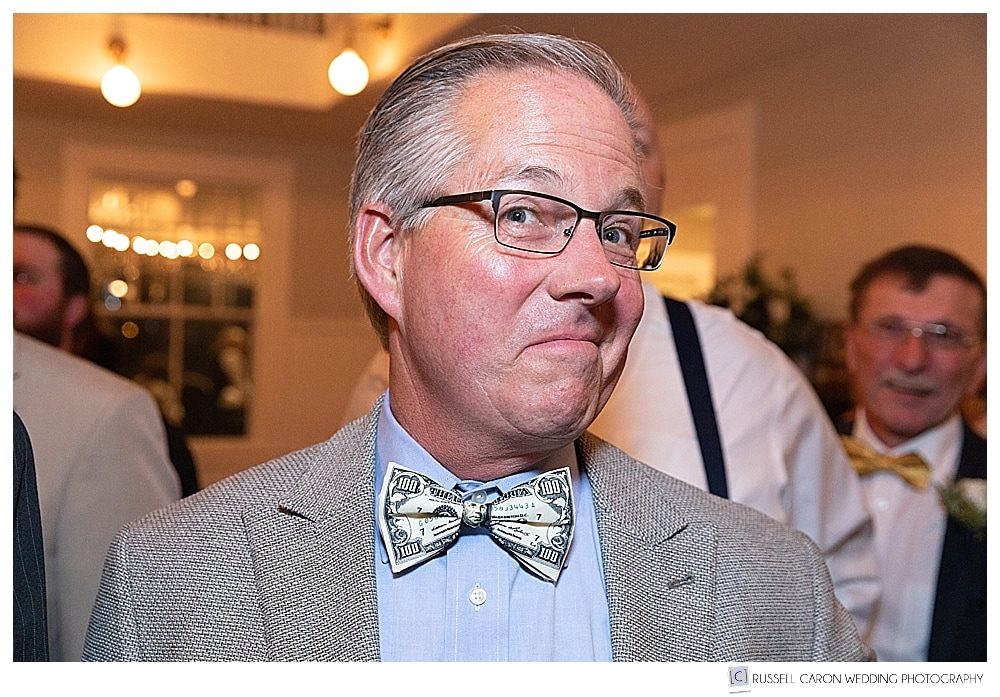 man wearing bow tie of one hundred dollar bill