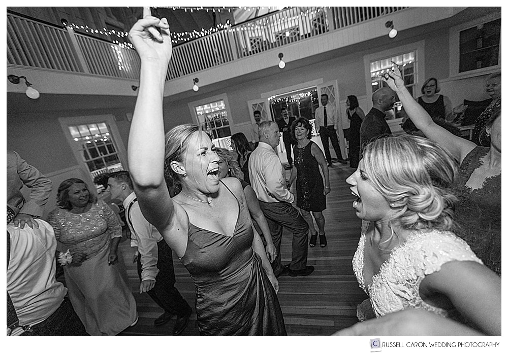 black and white photo of bride dancing with a wedding guest