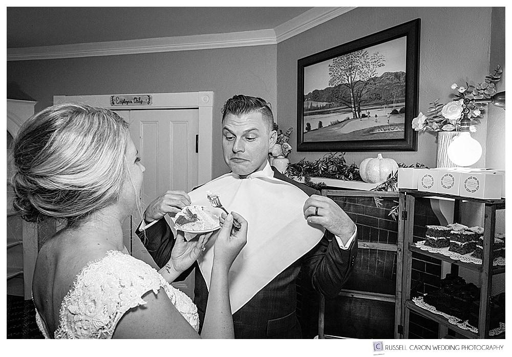 black and white photo of bride feeding groom cake