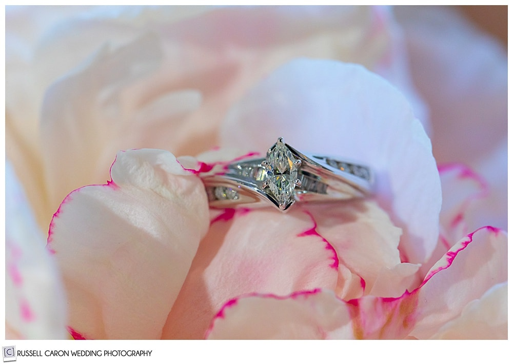 diamond engagement ring on a pink peony