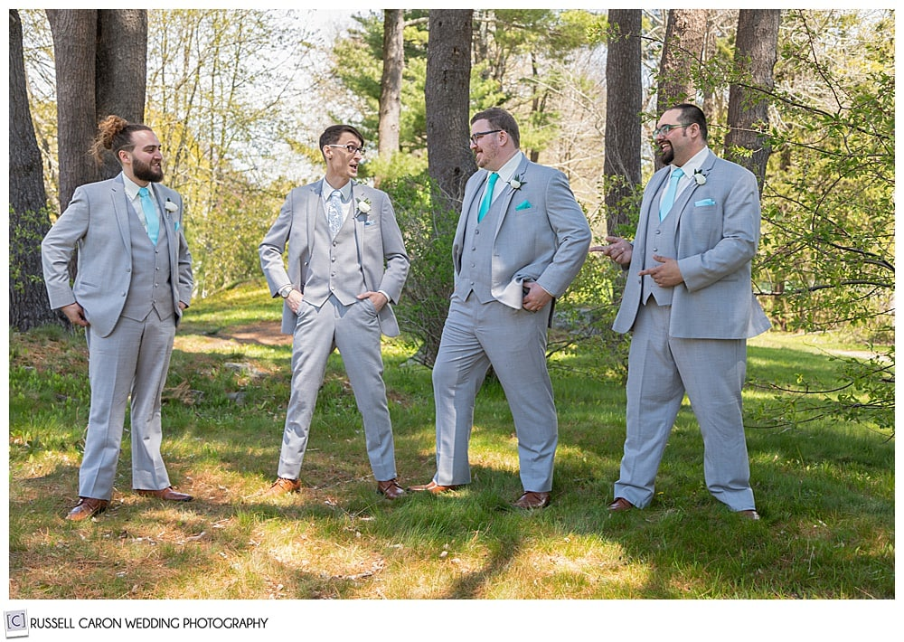 groom and groomsmen standing together and laughing