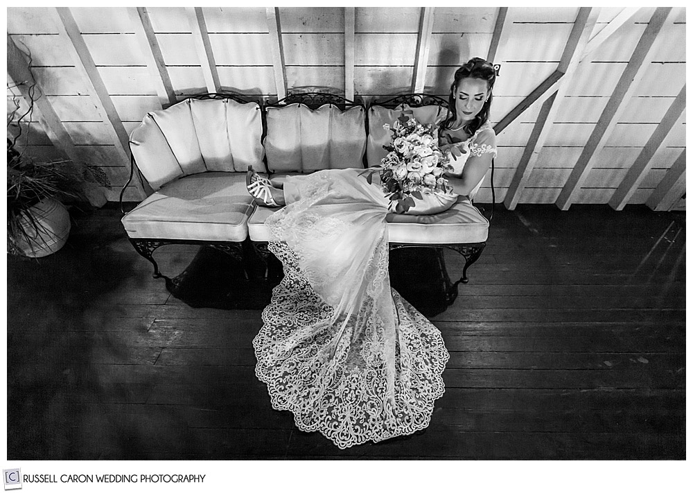 black and white photo of bride on a chaise holding her bouquet