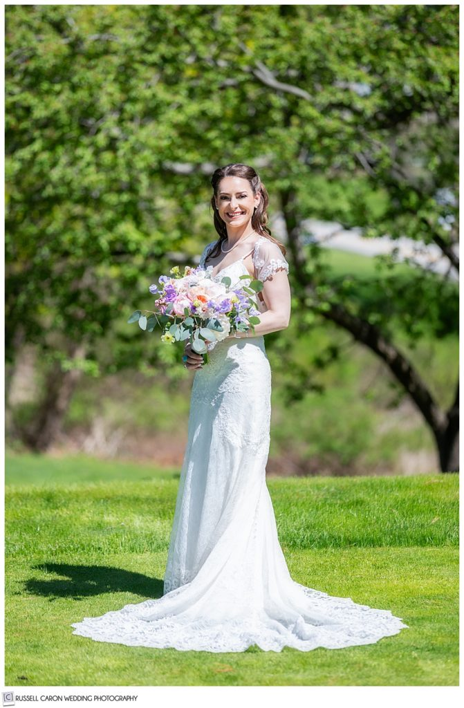 full length bridal portrait of a bride outside on a green lawn