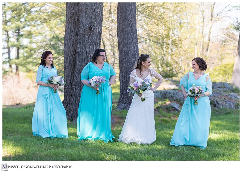 bride standing with bridesmaids in turquoise dresses