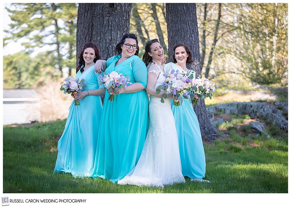 bride and bridesmaids standing close together and laughing